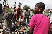 Alaba International Market. Kids showing what can be found on the neaby dump, old printer circuit boards, old TV casings and lots of CRT glass.<br /> New and old - and a lot of non-working electronic goods such as TVs and computers come in to the market via Lagos harbour from the US, Western Europe and China. This picture is part of an undercover investigation by Greenpeace and Sky News.  A TV-set originally delivered to a municipality-run collecting point in UK for discarded electronic products was tracked and monitored by Greenpeace using a combination of GPS, GSM, and an onboard radiofrequency transmitter placed inside the TV-set.  The TV arrived in Lagos in container no 4629416 and was found in Alaba International Market and bought back by Greenpeace activist. The TV was subsequently brought back to England and used as proof of illegal export of electronic waste. A number of individual are currently on trial in London in connection with illegal exports(Nov 2011)