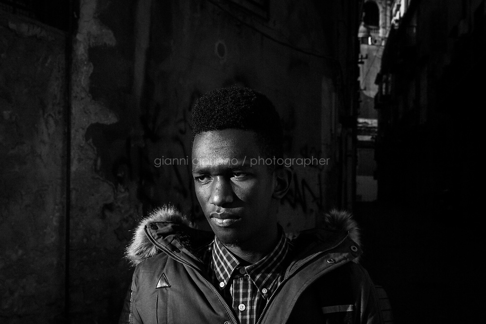 PALERMO, ITALY - 16 JANUARY 2019: Alieu Sosseh (17, from Gambia) poses for a portrait in Palermo, Italy, on January 16th 2019.<br /> <br /> The historic market Ballarò of Palermo, in the neighbourhood known as Albergheria, is the oldest and biggest among the markets of the city.<br /> For about half a century, after World War II, Ballarò was increasingly depopulated as families moved to airier suburbs. Today there are over 14 ethnicities in Ballarò and more than 25 languages spoken: migrant communities, students, professionals, historic merchants and new entrepreneurs coexist.