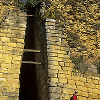 A traveler in Peru's Cordillera Central passes a narrow entrance between the imposing fortress walls at Kuelap, a stronghold of the pre-Incan Chachapoyan culture.