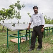 CAPTION: Janmanjoy Kumar Roy oversees DESI Power's experimental solar battery charging station. LOCATION: Gayari, Araria District, Bihar, India. INDIVIDUAL(S) PHOTOGRAPHED: Janmanjoy Kumar Roy.