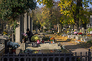 A lady puts flowers on a grave in Rakowicki cemetery in Krakow, Poland 2019.