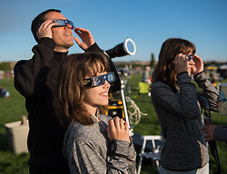 Klaus Koschinsky, left, and his daughters, Claudia, center, and Tanja, right, from Munich, Germany, are seen as they watch a total solar eclipse through protective glasses in Madras, Oregon on Monday, Aug. 21, 2017. A total solar eclipse swept across a narrow portion of the contiguous United States from Lincoln Beach, Oregon to Charleston, South Carolina. A partial solar eclipse was visible across the entire North American continent along with parts of South America, Africa, and Europe.  Photo Credit: (NASA/Aubrey Gemignani)