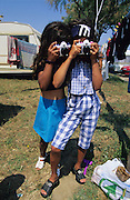 Young gitan girls playing with toy cameras with Spice Girls T-shirt<br /><br />Europe, France, Camargue, Saintes Maries de la Mer. The seaside town in the Camargue hosts a Gypsy festival once a year during May, where its landscape undergoes great changes. Otherwise it is a land bordered by sea, lakes and ponds, populated by flamengos, bulls and horses.