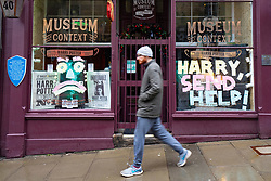 Edinburgh, Scotland, UK. 20 January 2020. Views of quiet streets in Edinburgh city centre on day after First minister Nicola Sturgeon announced national lockdown would be extended into February. Streets remain very quiet with no non essential shops open. Pic . Man walks past tourist  shop with Harry Potter themed messages in the window,  Iain Masterton/Alamy Live News
