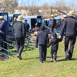 Gordonville, PA, USA - March 10, 2012: An Amish man walks around the mud sale with his sons.