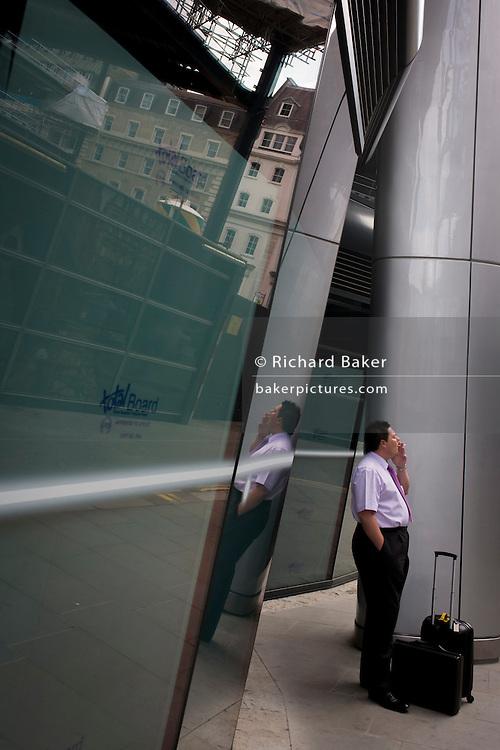 Businessman enjoys cigarette break beneath modern architecture on Walbrook, City of London.