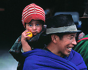 A father carries his watchful son on his back at the Indian market in Ambato, Ecuador.