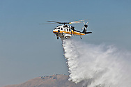 S-70 Firehawk on a demonstration airdrop run..Media day for LA county's firefighting aircraft at Van Nuys Airport. .2 Cl-425 Supercoopers on lease from Quebec. 1 Sikorsky S-70 Firehawk, and 1 Erickson Air-Crane helitanker were on display. .Fire season is expected to begin soon in LA with the arrival of the Santa Ana winds later this week.