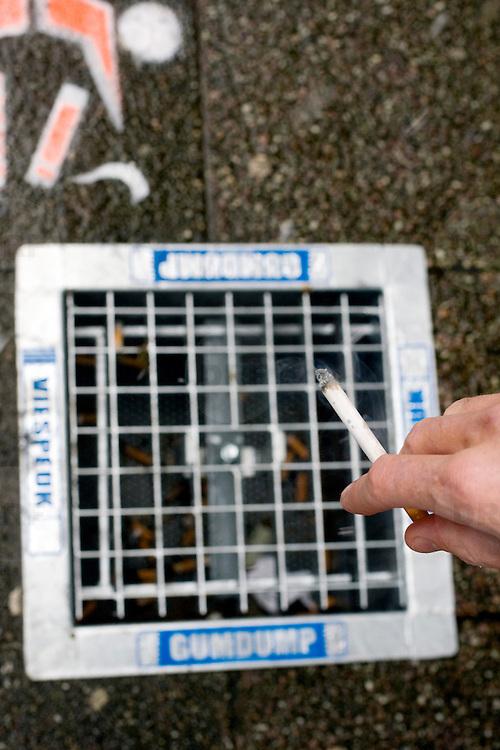 Nederland Rotterdam 23 november 2008 20081123 .De eerste asbaktegel van Nederland. De gemeente Rotterdam start als eerste gemeente van Nederland een proef met de asbaktegel. Gedurende drie maanden wordt op zes locaties in het centrum van de stad de asbaktegel getest. Sinds het rookverbod in openbare ruimtes, werkruimtes en de horeca roken er veel meer mensen op straat. Het gevolg hiervan is dat meer sigarettenpeuken op de stoep belanden. Een doorn in het oog van velen inwoners en bezoekers van de stad. De sigarettenpeuken ontsieren het straatbeeld en zijn slecht voor het milieu. Om de leefomgeving te ontlasten van de sigarettenpeuken is een  oplossing bedacht: de asbaktegel. De tegel is een asbak voor in de buitenruimte die in de stoep is verzonken. De bovenkant is een rooster waar sigarettenpeuken en kauwgom in gedeponeerd kunnen worden. Rotterdam is the first city to start a trial with an ashtray tile. Since the prohibition of smoking in public areas, more people are smoking on the streets. That results in more cigarettes on the streets. ..Foto: David Rozimg