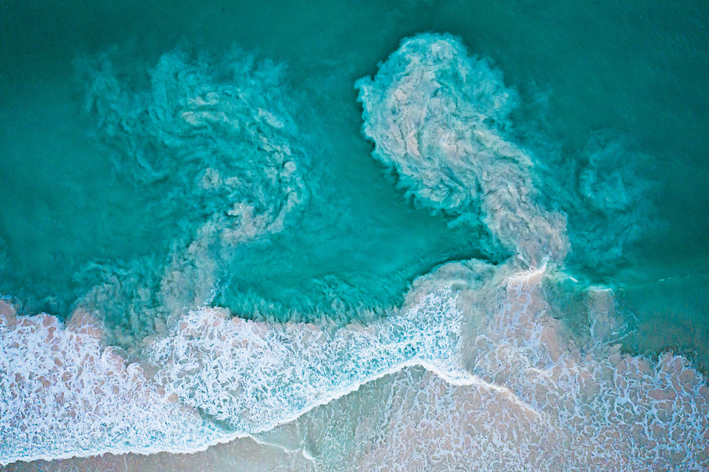 Waves crash along a beach and carry sediments back out to sea in The Bahamas.