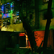 A man returns to his home at night in a colorful street.
