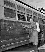 Y-480722B-02.  Worker spraying in roll-up window track. 900 bus victim of Vanport flood. Before restoration. Detail shots. Cleaning, paint shop. July  22, 1948