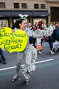 "New York, NY, USA-27 March 2016. Marni Halasa, a familiar fixture at New York City parades and other events, on roller skates and with a sign reading ""Bunnies vs. Corporarte Greed."""