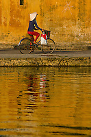 Woman riding a bicycle along Hoi An's waterfront lined with old french colonial architecture in gorgeous late afternoon light.