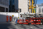 Construction traffic marshals stand against a hoarding surrounding a new project on Fenchurch Street in the City of London, the capitals financial district, on 29th July 2020, in London, England.