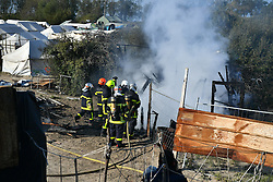 © Licensed to London News Pictures. 25/10/2016. Calais, France.  Building being set on fire  at the migrant camp in Calais, known as the 'Jungle'. French authorities have moved thousands of refugees and migrants living at the makeshift living area on the French coast, with some still refusing to leave. . Photo credit: Ben Cawthra/LNP