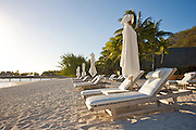 Chaise lounges on the beach at the Bora Bora Nui Resort & Spa. Previously a Starwood Luxury Collection property, the Bora Bora Nui is now operated by Hilton. Bora Bora is one of the Leeward Islands in the Society Islands archipelago of French Polynesia.