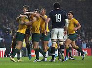 Australians celebrate whilst Scotland's Tim Swinson looks on during the Rugby World Cup Quarter Final match between Australia and Scotland at Twickenham, Richmond, United Kingdom on 18 October 2015. Photo by Matthew Redman.