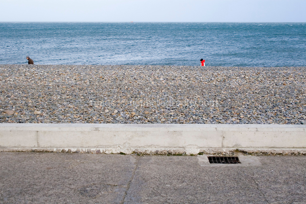 Two people walking along the beach at Bray in Wicklow Ireland in the winter