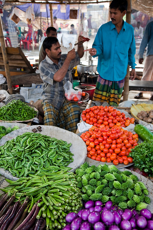 A vendor weighs tomatoes on scales at the sprawling Sonargaon market  in Sonargaon, outside Dhaka, Bangladesh.