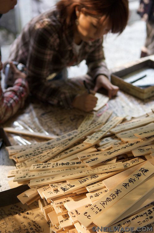 A Japanese University student writes prayers for good grade in this year's exams at a Shinto shrine in Kyoto, Japan.