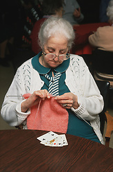 Elderly woman sitting at table in residential home knitting,