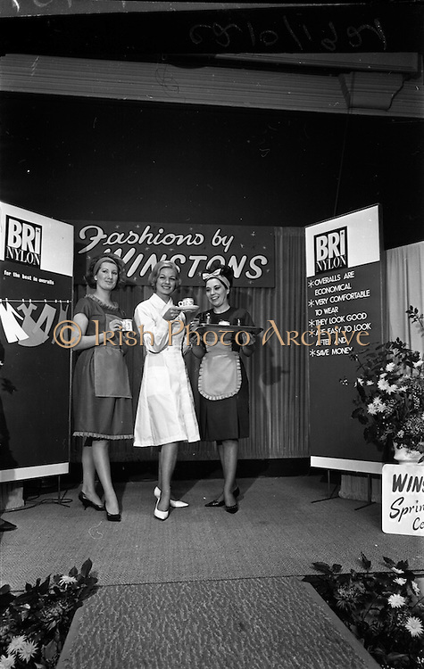 14/01/1963<br /> 01/14/1963<br /> 14 January 1963<br /> Opening of Irish Hotel and Catering Trades Exhibition at the Mansion House, Dublin. Waitress's aprons (left and right) and a Bri-Nylon white novelty weave receptionists coat , all from Winstons, Dublin, pictured during a fashion parade held in conjunction with the exhibition.
