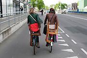 Twee meisjes fietsen met stoelen achterop de fiets door Utrecht.<br /> <br /> Two girls are cycling with chairs in Utrecht.