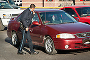 A Juarez police officer looks into the vehicle where moments earlier assigns shot dead a former policeman during morning rush hour along a main road in Juarez, Mexico January 16, 2009. The shooting, believed linked to the ongoing drug war which has already claimed more than 40 people since the start of the year. More than 1600 people were killed in Juarez in 2008, making Juarez the most violent city in Mexico.    (Photo by Richard Ellis)