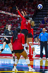 BLOOMINGTON, IL - September 14: Anne-Marie Watson strikes past Emmy Ogogor and Kaity Weimerskirch during a college Women's volleyball match between the ISU Redbirds and the University of Central Florida (UCF) Knights on September 14 2019 at Illinois State University in Normal, IL. (Photo by Alan Look) Official in background - Dean Hoskin