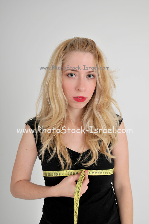 Body image - disappointed young woman measures her bosom