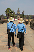Two tour guides dressed in uniform walk along the stone walkway surrounding Ankor Wat temple complex in Krong Siem Reap, Cambodia. Angkor Wat is a temple complex in Cambodia and the largest religious monument in the world, with the site measuring 162.6 hectares. It is Cambodia's main tourist destination.  (photo by Andrew Aitchison / In pictures via Getty Images)