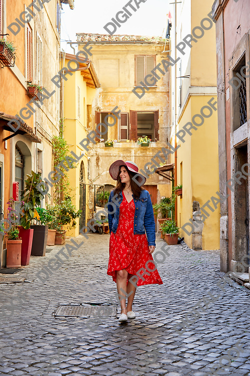 Happy woman in dress and hat walking on paved old street of Rome looking happily around.