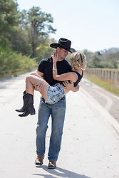 cowboy carrying a beautiful girl on a rural dirt road
