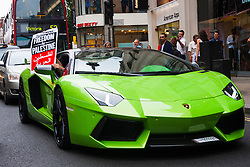 """London, July 5th 2014. A passenger in a foreign-registered Lamborghini supports a protest near the Israeli embassy in London, against the ongoing occupation of Palestine and the west's support of """"Israel's collective punishment of Palestinians""""."""