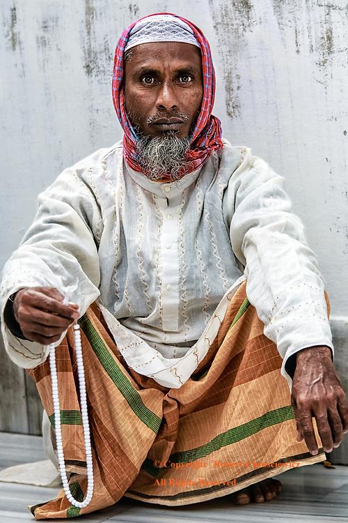 Prayer Beads: A bearded man, in traditional dress, holds his prayer beads as he squats down in Hazrat Shahjalal Mazar Sharif, Sylhet Bangladesh.