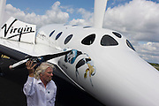 Alongside his SpaceShipTwo vehicle, Richard Branson holds model of satellite LauncherOne after Virgin Galactic space tourism presentation at Farnborough