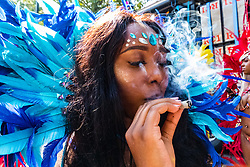 A woman exhales smoke from a hand-rolled cigarette as day two of the Notting Hill Carnival in West London is in full swing, as performers floats form the procession in what is known as Europe's biggest Street Party. London, August 26 2019.