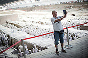 A Chinese man takes a selfie on the panoramic terrace of the Terracotta Warriors historical site in Xian, Shaanxi, July 31, 2014.<br /> <br /> Smartphones are an essential tool of Chinese ordinary life. Everywhere in China, people use them to take pictures to share online, to talk and chat, to play videogames, to get access to the mainstream information, to get connected one each other. In the country where the main global social media are forbidden - Facebook, Twitter and Youtube are not available  -, local social networks such as WeChat have a wide spread all over the citizens. The effect is an ordinary and apparently compulsive way to get easy access to digital technology and modern way of communication. <br /> A life through the display. Yes, We Chat.<br /> <br /> © Giorgio Perottino