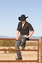 hot cowboy sitting on a fence overlooking mountains