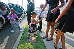 14 September 2013. Prayer Tower Church of God in Christ. New Orleans, Louisiana. <br /> Family members arrive for the funeral for 11 yr old Arabian 'Ray Ray' Gayles, fatally shot September 2nd. Arabian was cradling a 1 yr old cousin whilst sat on the couch at home when gunmen pulled up outside and sprayed the house with bullets. Arabian was hit in the head and died shortly afterwards. NOPD is questioning 2 men in connection with the murder.<br /> Photo; Charlie Varley