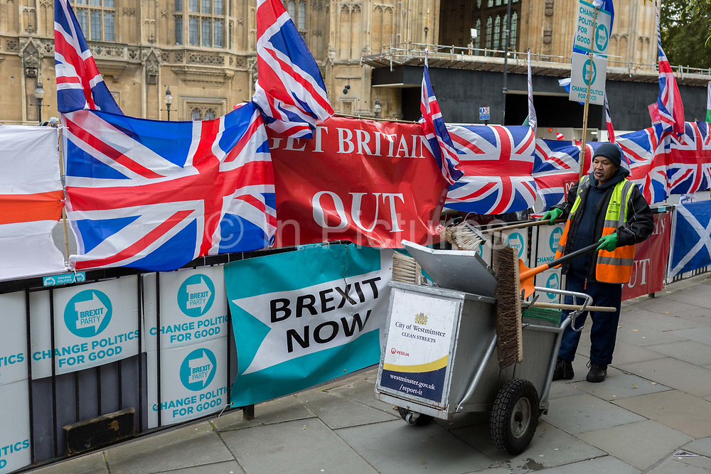 On the day that the EU in Brussels agreed in principle to extend Brexit until 31st January 2020 aka Flextension and not 31st October 2019, a Westminster borough street cleaner picks up litter next to Brexit Party flags and banners during a Brexit protest outside parliament, on 28th October 2019, in Westminster, London, England.