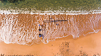 Aerial view of people walking with a kayak at Sant Pol beach, Girona, Spain.