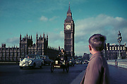 A young boy watches classic and vintage cars driving over Westminster Bridge and under Big Ben as part of the RAC London to Brighton Car Rally, in the winter of 1971, on 7th November 1971, in London, England.