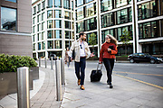 Work colleagues walking to a meeting holding a tablet, work folder and suitcase in the banking and fincance area of St Helier, Jersey, CI