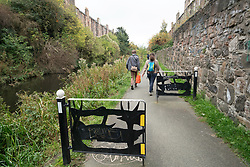 Couple walking along towpath beside the Union Canal  in Edinburgh, Scotland, United Kingdom.