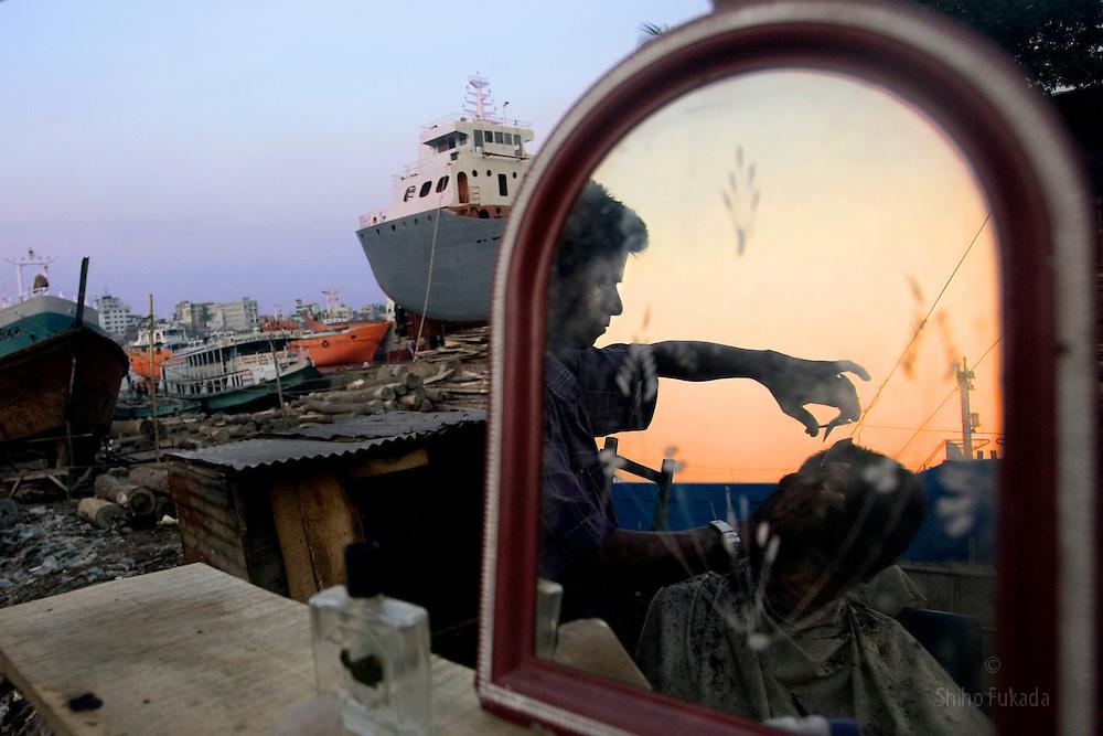 A labor gets hair cut in a ship yard in Dhaka, Bangladesh.