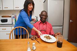 Elderly black man with white woman carer serving his dinner