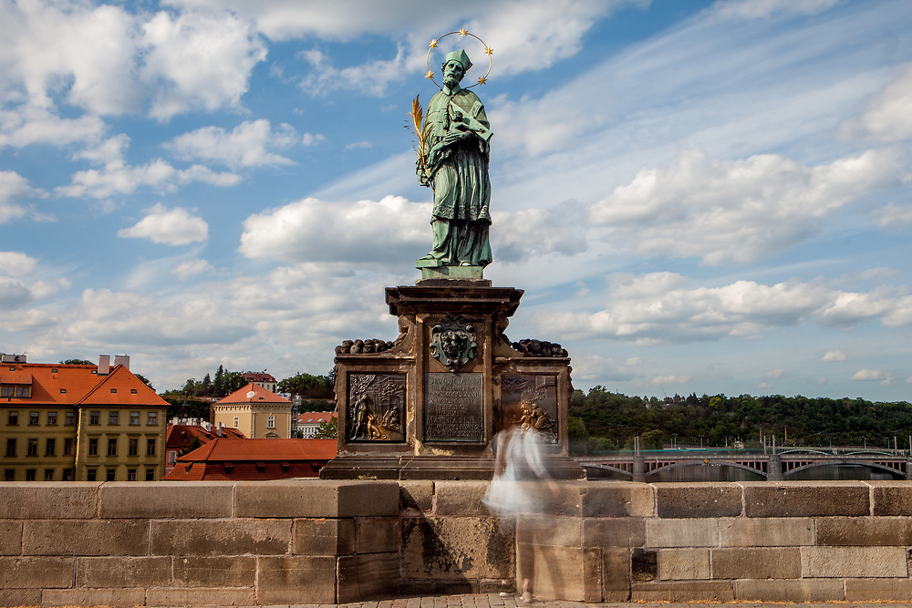 """A woman standing in-front of the statue of  """"John of Nepomuk"""" which is an outdoor sculpture, installed in 1683 on the north side of the Charles Bridge in Prague, Czech Republic. The Czech government lowered the security measures and as of Monday 25 May 2020, wearing of protective masks will be mandatory only in the interiors of buildings other than the place of residence and in public transport."""