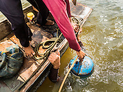 14 OCTOBER 2015 - BANGKOK, THAILAND: A spotter helps a diver go back to the bottom of the Chao Phraya River in Bangkok. Divers work in two man teams on small boats in the Chao Phraya River. One person stays in the boat while the diver scours the river bottom for anything that can be salvaged and resold. The divers usually work close to shore because the center of the river is a busy commercial waterway with passenger boats and commercial freight barges passing up and down the river all day long. The Chao Phraya is a dangerous river to dive in. It's deep, has large tidal fluctuations, is fast flowing and badly polluted. The divers make money only when they sell something.    PHOTO BY JACK KURTZ
